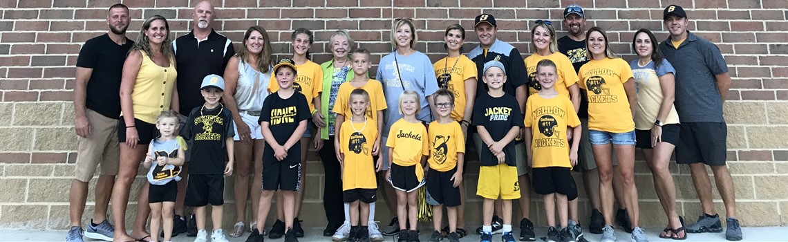Family members ranging in ages from middle age to preschool stand next to a brick wall wearing black and yellow spirit clothing.