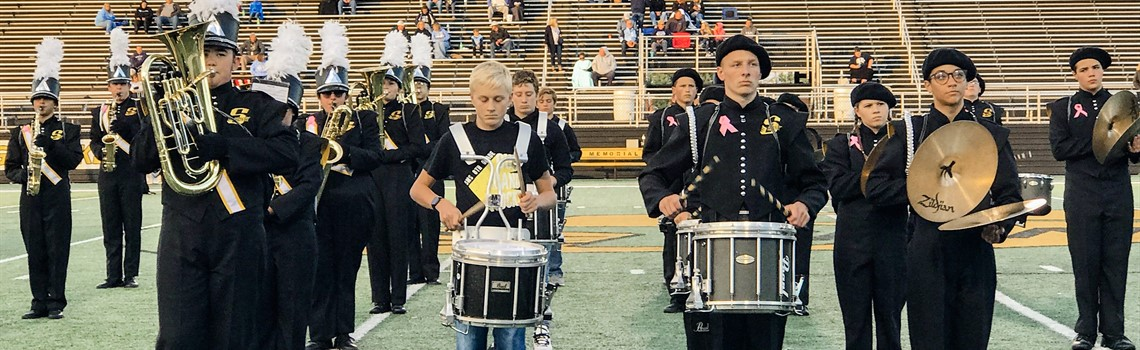 Eighth-grade band members stand alongside The Pride of Sidney during the pregame ceremonies.