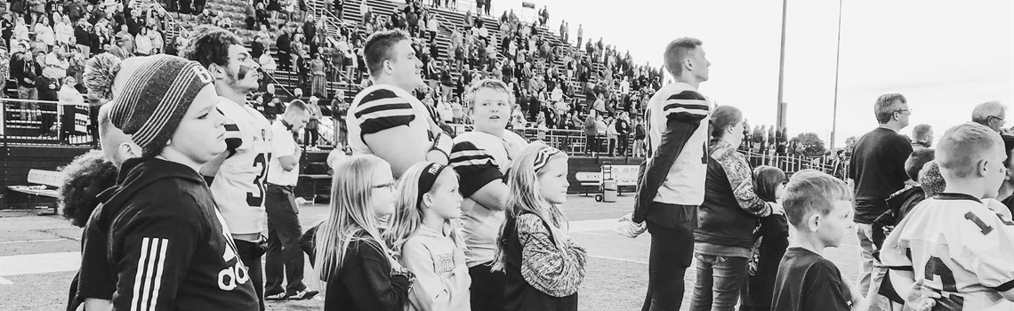 Black & white photo elementary students stand with hands over hearts with the SHS football team for the playing of the National Anthem during Elementary Night!