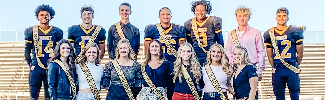 Sidney High School Homecoming Court 2020 - 7 teenage females stand in a row in front of 7 teenage males, all wearing Homecoming Court Sashes.