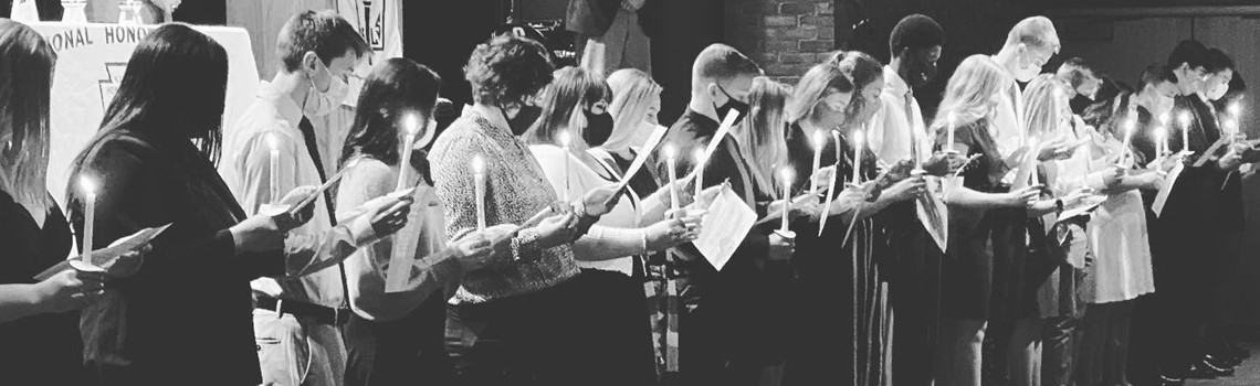 High school students, dressed up, stand in a line while holding lit candles and certificates as a part of the National Honor Society induction ceremony.