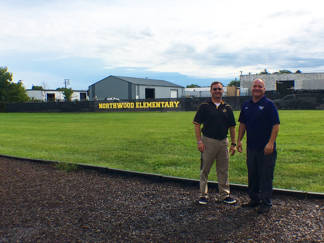 Northwood Principal Eric Barr and Sidney Tire owner Jeff Pollard check out the new fence between the school and Sidney Tire.